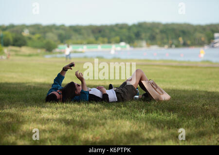 Two young people relaxing after work on grass in park - Stock Photo