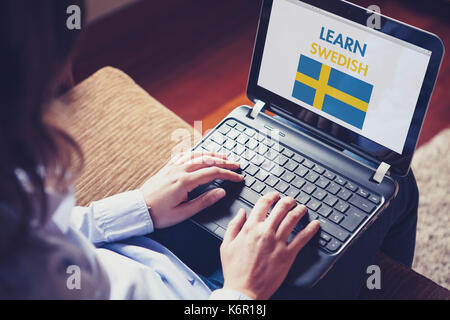 Woman using a laptop computer to learn Swedish by internet - Stock Photo