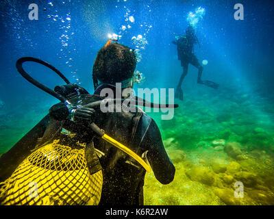Scuba diver swimming in the bottom of the sea - Stock Photo