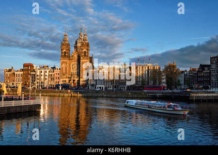 Tourist boat in Amsterdam canal and Church of Saint Nicholas on  - Stock Photo