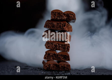 Porous chocolate in stack on a black background closeup. Pieces of milk chocolate, lined up in a tower, shrouded - Stock Photo