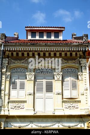 Traditional Singapore shop house with dormer roof windows and wooden shutters in historic Kampong Glam - Stock Photo