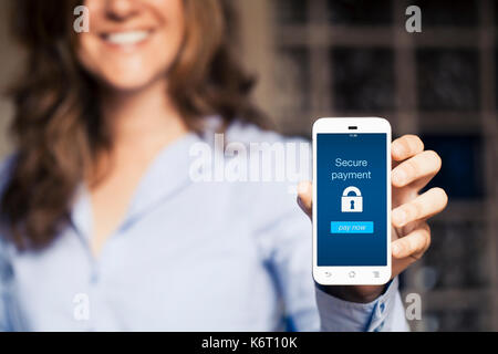 Secure payment notification in a mobile phone screen. Woman using a smartphone with online banking app in the screen. - Stock Photo