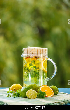 Water with lime, orange and lemon served in a glass jug - Stock Photo