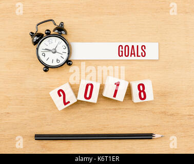 Goals 2018 year red on wood cube with pencil and clock top view on wood table,New year business concept. - Stock Photo