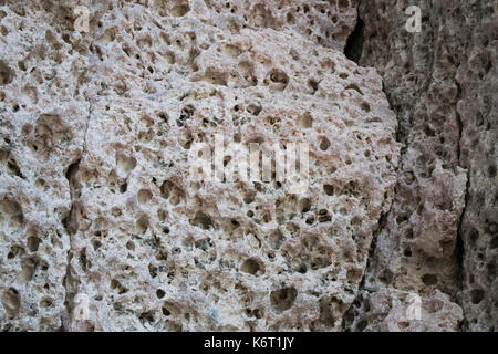 Pale pink or pinkish limestone rock found along the cliffs of South-West Malta. Rocks are full of holes by weathering - Stock Photo