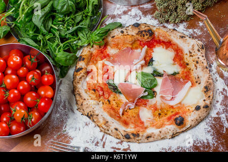 Traditional italian pizza with mozzarella, tomato, ham and ingredients on wooden table - Stock Photo