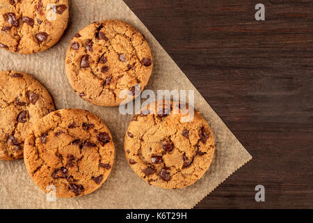 Chocolate chips cookies on baking paper with copyspace - Stock Photo