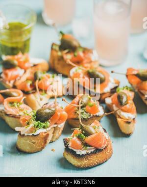 Crostini with smoked salmon and pink grapefruit cocktails - Stock Photo