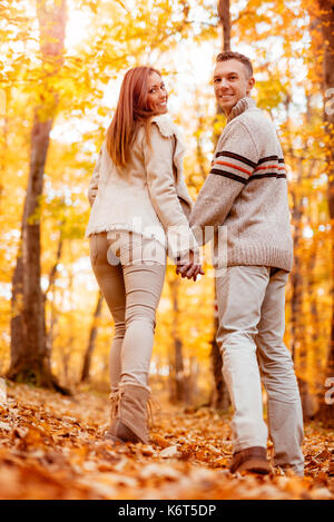 Beautiful smiling couple walking in sunny forest in autumn colors. Looking at camera, rear vew. - Stock Photo
