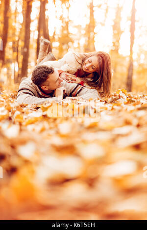 Beautiful smiling couple enjoying in sunny forest in autumn colors. They are lying on the falls leaves and having - Stock Photo