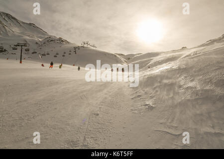 Skiing area with skiers and snowboarders in tyrolean Alps. Beautiful winter panoramic landscape. Bright sunny day - Stock Photo