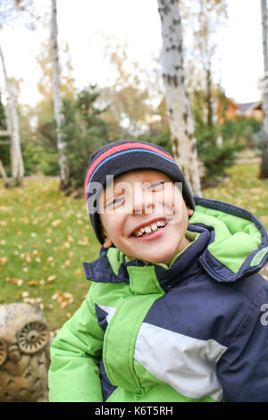 A funny cheerful toddler boy in a warm jacket and hat smiling or laughing at beautiful autumn garden , close up. - Stock Photo