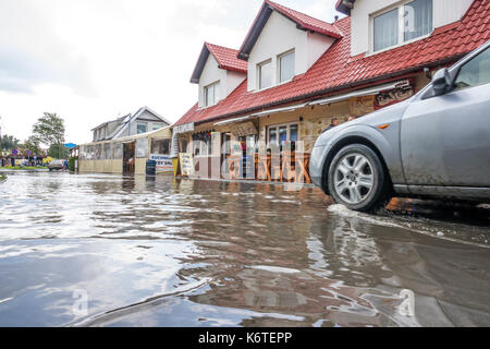Sarbinowo, Poland -  August 2017 : Car going through the flooded street after extremely heavy rainfall - Stock Photo