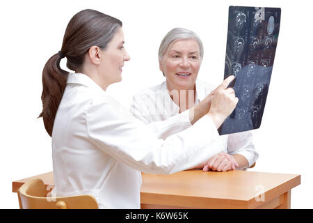 Female middle aged doctor showing her senior patient an mri of her head, isolated on white background - Stock Photo