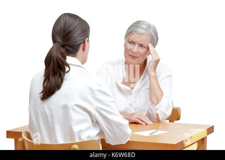 Female doctor with her senior patient with sleeping trouble, suffering of splitting headache or migraine, isolated - Stock Photo