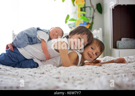 Two children, toddler and his big brother, hugging and kissing their newborn baby brother at home, few days after - Stock Photo