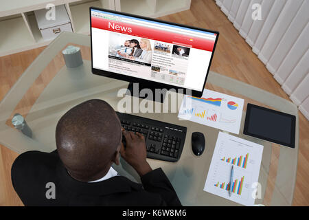 Young African Businessman Looking At Business News On Computer In Office - Stock Photo