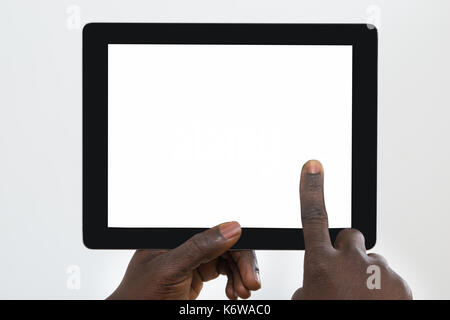 Close-up Of Person's Hand Using Digital Tablet With Blank Screen - Stock Photo