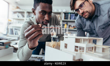 Two male architects in office discussing construction project. Young men working together on new building model. - Stock Photo