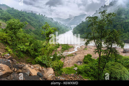 The Kameng river flanked by forested slopes and boulders on a misty monsoon day as viewed from National Highway - Stock Photo