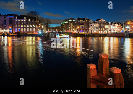 Bridge in the old town of Amsterdam in the evening - Stock Photo