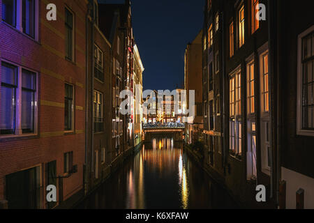 Narrow canal in the old town of Amsterdam in the evening - Stock Photo