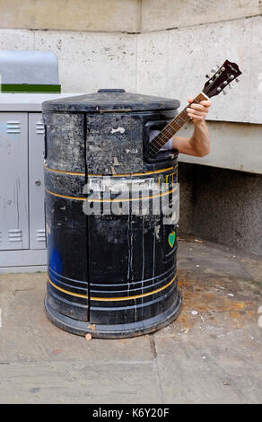 busker in a litter bin, cambridge, england - Stock Photo