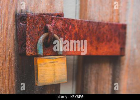 Rusty padlock on wooden door - Stock Photo