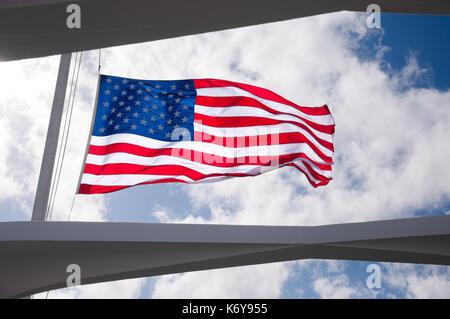 American Flag flying half mast as seen through the roof of the USS Arizona Memorial in Pearl Harbor, Hawaii - Stock Photo