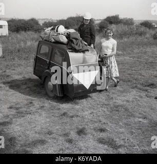 Early 1950s, Britain, mother and son stand outside in a grassy field beside their motorcycle and two wheeled sidecar - Stock Photo