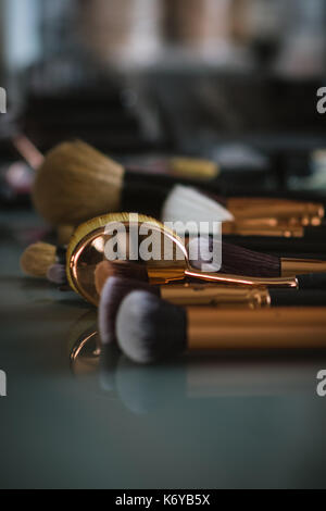 Set of professional makeup brushes on glass table with shallow depth of field - Stock Photo