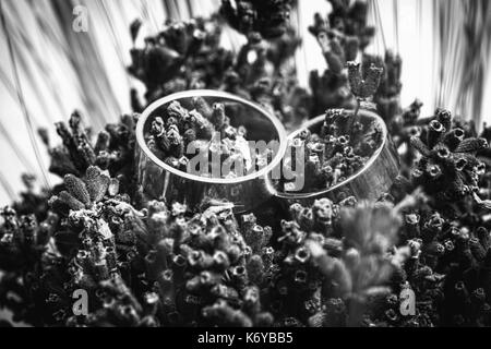 Macro shot of simple design wedding rings in bouquet of flowers - Stock Photo