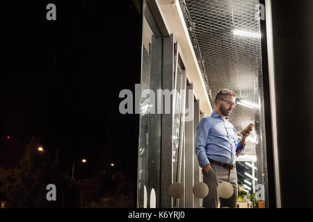 Businessman in the office at night working late. - Stock Photo