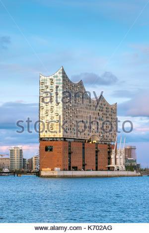 Germany, Hamburg, HafenCity. Elbphilharmonie (Elbe Philharmonic Hall) concert hall on the Elbe River at sunset. - Stock Photo