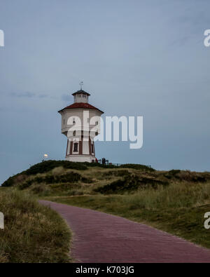 Wasserturm Langeoog. Germany Deutschland.  Soon after twilight there is a moonrise occurring behind the water tower, - Stock Photo