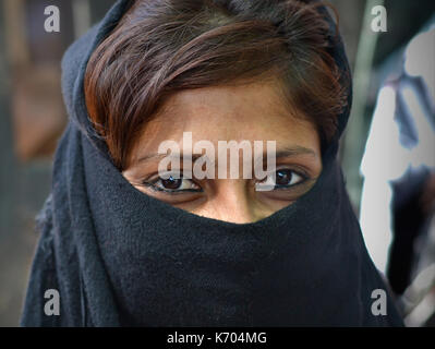 Young Indian Muslimah with smiling eyes and casual black niqab; Ahmedabad, Gujarat, Western India - Stock Photo