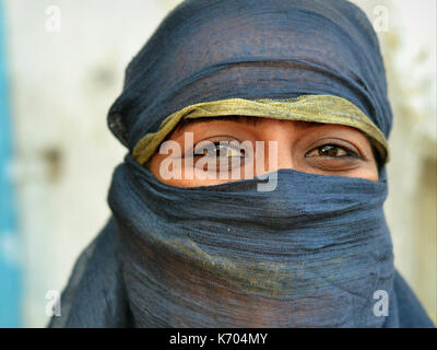 Mature Indian Muslimah with smiling eyes and black niqab; Ahmedabad, Gujarat, Western India - Stock Photo