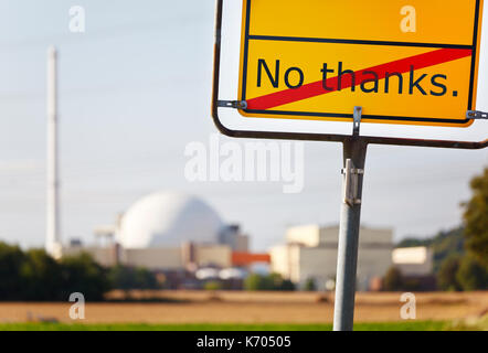 A yellow sign saying No thanks in front of a nuclear power station. - Stock Photo