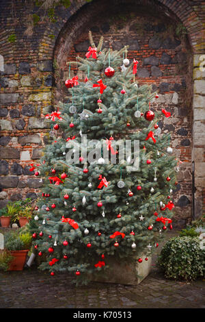 A decorated outdoor christmas tree in front of an old wall. - Stock Photo