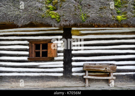 Old house with small wooden window and bench in a vintage romanian village style - Stock Photo
