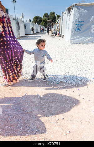 As they walk past rows of emergency homes, a boy holds on to his mother's dress. She walks on as he is distracted - Stock Photo