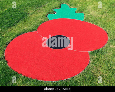 Remembrance Day Poppy, logo, symbol, set in turf, lawn, grass, Hunstanton, Norfolk, England, UK, war memorial, memorials, - Stock Photo