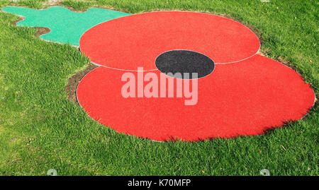Remembrance Day Poppy, logo, emblem, symbol, set in turf, lawn, grass, Hunstanton, Norfolk, England, UK, war memorial, - Stock Photo