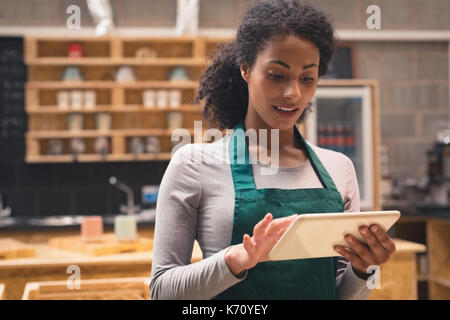 Smiling beautiful waitress using digital tablet in café - Stock Photo
