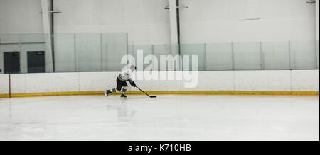 Male player practicing ice hockey at rink - Stock Photo