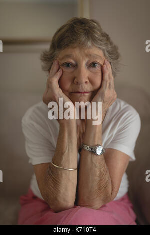 Portrait of senior woman sitting on sofa in living room - Stock Photo