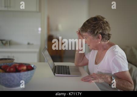 Tense senior woman using laptop in kitchen at home - Stock Photo