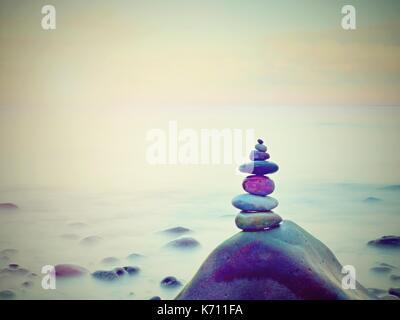 Stones pyramid on pebble beach symbolizing stability, zen, harmony, balance. Tropical sea beach. - Stock Photo