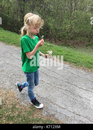 Little girl blowing dandelion while on a walk and listening to music - Stock Photo